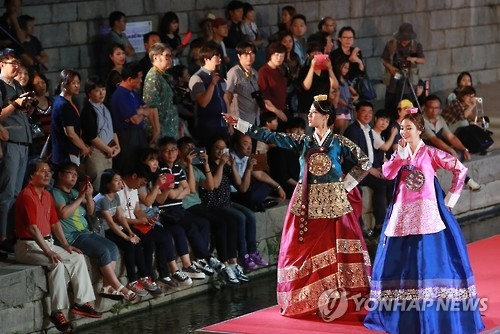 Female models walk on a stage set on Cheonggye Stream in downtown Seoul during a hanbok fashion show held on Sept. 10, 2016. (Yonhap)