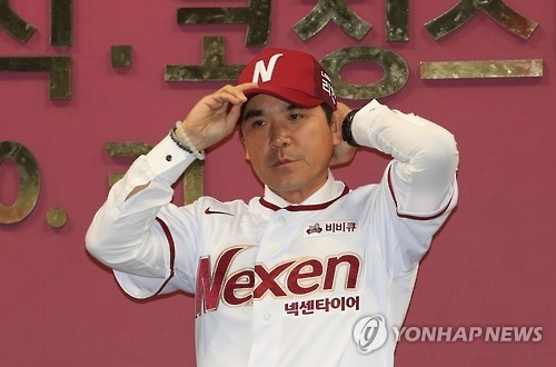 Jang Jung-suk, newly named manager of the Nexen Heroes baseball club, dons the team's hat during his inauguration ceremony at Gocheok Sky Dome in Seoul on Oct. 31, 2016. (Yonhap)