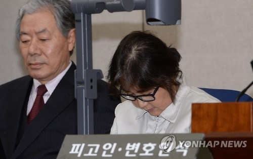 Dressed in a prison uniform, Choi Soon-sil, a close confidante of President Park Geun-hye, lowers her head while sitting in the dock during the first preparatory hearing at the Seoul Central District Court in southern Seoul on Dec. 19, 2016. She is at the center of the influence-peddling scandal that has led to Park's impeachment. On the left is her lawyer, Lee Kyung-jae. (Press corps-Yonhap)