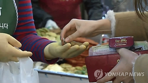 A consumer pays in cash at a South Korean market in a file photo provided by Yonhap News TV. (Yonhap)