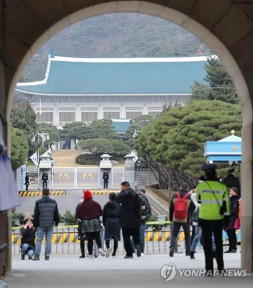 This file photo, taken on Nov. 30, 2016, shows a group of tourists looking at the main gate of the presidential office Cheong Wa Dae in Seoul. (Yonhap)