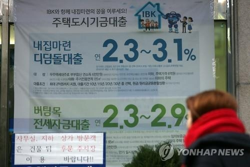 A woman passes by an ad placard on mortage loans in this file photo. (Yonhap)
