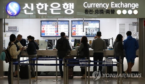 Travelers exchange currencies at Incheon International Airport in this undated file photo. (Yonhap)