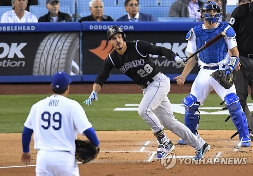 In this Associated Press photo, Nolan Arenado of the Colorado Rockies (C) watches his two-run home run off Ryu Hyun-jin of the Los Angeles Dodgers (L) in the first inning at Dodger Stadium in Los Angeles on April 18, 2017. (Yonhap)
