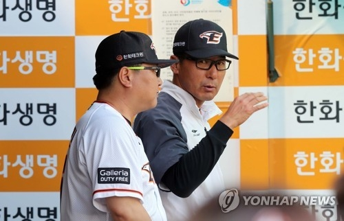 In this file photo taken on May 24, 2017, Lee Sang-kun (R), interim manager of the Hanwha Eagles, speaks with a coach during a Korea Baseball Organization regular season game against the Kia Tigers at Hanwha Life Eagles Park in Daejeon. (Yonhap)