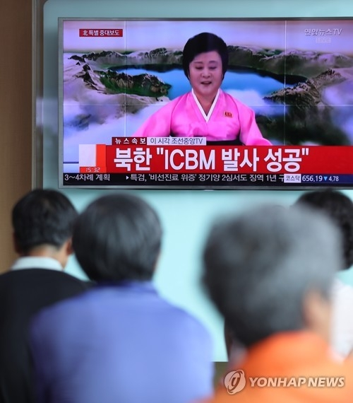 This photo taken on July 4, 2017, shows South Korean citizens watching an announcement by North Korea over its claimed successful launch of an intercontinental ballistic missile. (Yonhap)