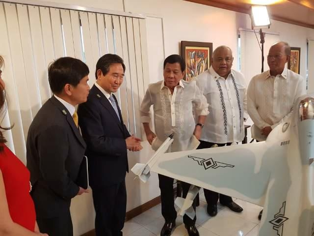 In this photo taken on July 4, 2017, KAI President & CEO Ha Sung-yong (second from left) and Philippine President Rodrigo Duterte (3rd from left) look at a miniaturized FA-50PH at Clark Air Base in the Philippines Tuesday. (Yonhap)