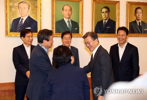 President Moon Jae-in (2nd from R) shakes hands with Culture Minister Do Jong-hwan before the start of a weekly Cabinet meeting at his office, Cheong Wa Dae, in Seoul on July 11, 2017. (Yonhap)