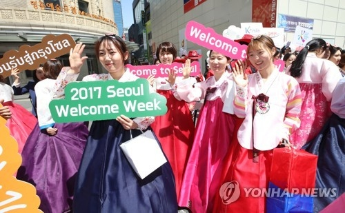 "In this file photo taken on April 27, 2017, tourism officials, dressed in the traditional costume ""hanbok,"" march through the Myeongdong shopping district in downtown Seoul to mark the 2017 Seoul Welcome Week for foreign tourists. (Yonhap)"