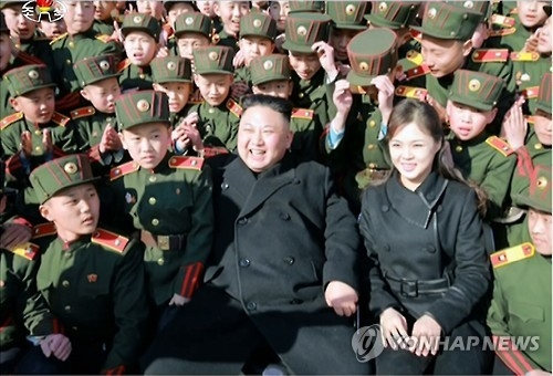This photo, released by the North's Korean Central Television on March 3, 2017, shows North Korean leader Kim Jong-un and his wife Ri Sol-ju meeting students of the Red Flag Mangyongdae Revolutionary School in Pyongyang. (For Use Only in the Republic of Korea. No Redistribution) (Yonhap)