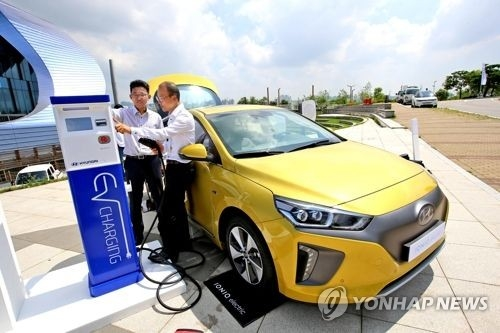 In this undated file photo, customers try to charge the all-electric Ioniq EV car. (Yonhap)