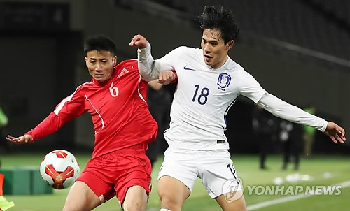 South Korea's Jin Seong-uk (R) vies for the ball against North Korea's Kang Kuk-chol during a match between South and North Korea at the EAFF E-1 Football Championship at Ajinomoto Stadium in Tokyo on Dec. 12, 2017. (Yonhap)
