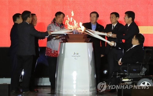 Eight torches held by eight representatives, including Paralympic and government officials, are joined to create a single flame during the torch lighting ceremony of the PyeongChang Paralympic Games at Olympic Park in eastern Seoul on March 3, 2018. (Yonhap)