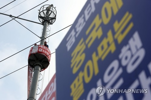 In this photo taken March 9, 2018, Kumho Tire's union leaders continue their demonstration atop a utility pole near the tiremaker's plant in Gwangju, 330 km south of Seoul, in protest against creditors' plan to sell it to Qingdao Doublestar. (Yonhap)
