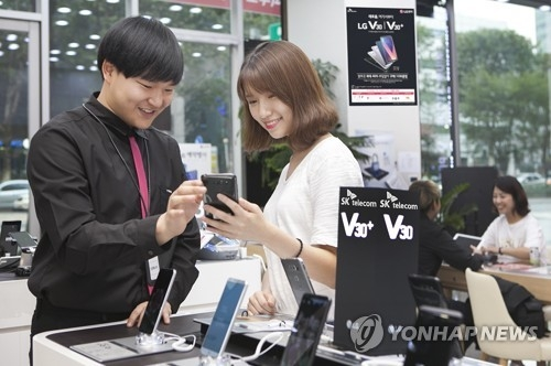 Models pose with LG Electronics' V30 smartphone in this file photo released by SK Telecom Co. on September 20, 2017. (Yonhap)