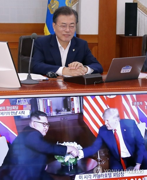 South Korean President Moon Jae-in (top) watches the live broadcast of a historic summit between U.S. President Donald Trump and North Korean leader Kim Jong-un in Singapore before the start of a Cabinet meeting at his presidential office Cheong Wa Dae in Seoul on June 12, 2018. (Yonhap)