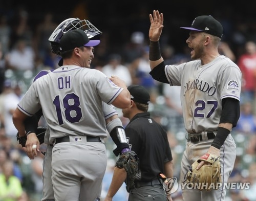 In this Associated Press photo, Oh Seung-hwan of the Colorado Rockies (L) celebrates his save with shortstop Trevor Story after beating the Milwaukee Brewers 5-4 in a Major League Baseball regular season game at Miller Park in Milwaukee on Aug. 5, 2018. It was Oh's first save for the Rockies since arriving in a trade from the Toronto Blue Jays on July 26, 2018. (Yonhap)