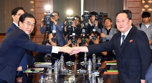 This photo taken by the joint press corps shows South Korea's Unification Minister Cho Myoung-gyon (L) shaking hands with his North Korean counterpart Ri Son-gwon before launching high-level talks on Aug. 13, 2018, on the northern side of Panmunjom to discuss inter-Korean relations and preparations for a summit meeting between their leaders. (Yonhap)