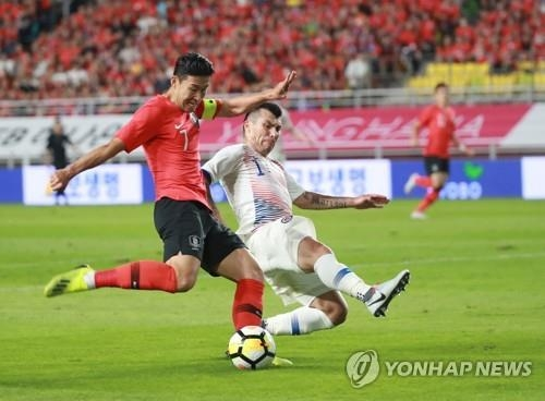South Korea's Son Heung-min (L) tries to take a shot against Chile's Gary Medel during a friendly football match at Suwon World Cup Stadium in Suwon, south of Seoul, on Sept. 11, 2018. (Yonhap)