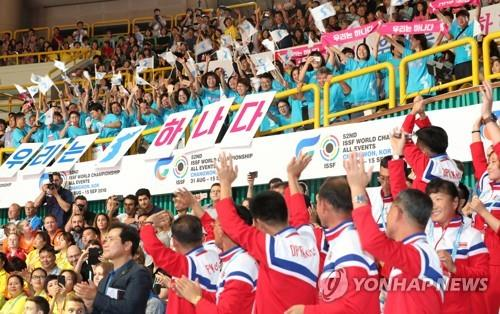 In this file photo from Sept. 1, 2018, North Korean athletes and officials greet their supporters in the stands at Changwon Gymnasium during the opening ceremony of the International Shooting Sport Federation (ISSF) World Championship in Changwon, 400 kilometers southeast of Seoul. (Yonhap)