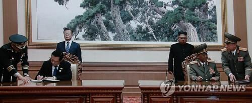 Defense Minister Song Young-moo and his North Korean counterpart, No Kwang-chol, sign an agreement on reducing tensions in Pyongyang on Sept. 19, 2018, in this photo captured from a screen at the press center in Seoul. (Yonhap)