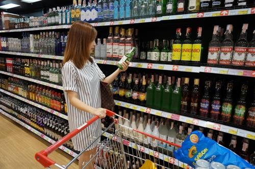This photo, provided by Hite Jinro Co., shows a customer selecting a soju product. (Yonhap)