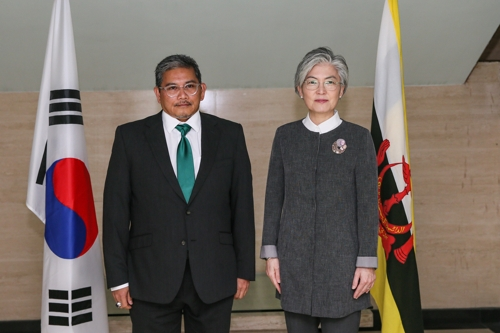 This photo provided by the South Korean Ministry of Foreign Affairs shows Foreign Minister Kang Kyung-wha (R) and Brunei's Foreign Minister Erywan Yusof posing for photos during their talks in Bandar Seri Begawan, Brunei, on Jan. 12, 2019. (Yonhap)