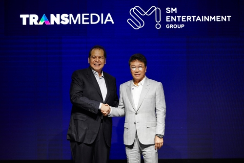 This photo provided by SM Entertainment shows SM founder Lee Soo-man (R) and Chairul Tanjung, the chairman of CT Corp, shaking hands on Feb. 21, 2019, in Jakarta, Indonesia, after signing an agreement to set up a joint venture. (Yonhap)