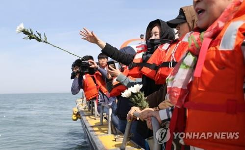 Bereaved family members and relatives of Danwon High School students killed in the 2014 sinking of the Sewol ferry throw flowers into the sea off Jindo, South Jeolla Province, on April 16, 2019, marking the fifth anniversary of the disaster. (Yonhap)