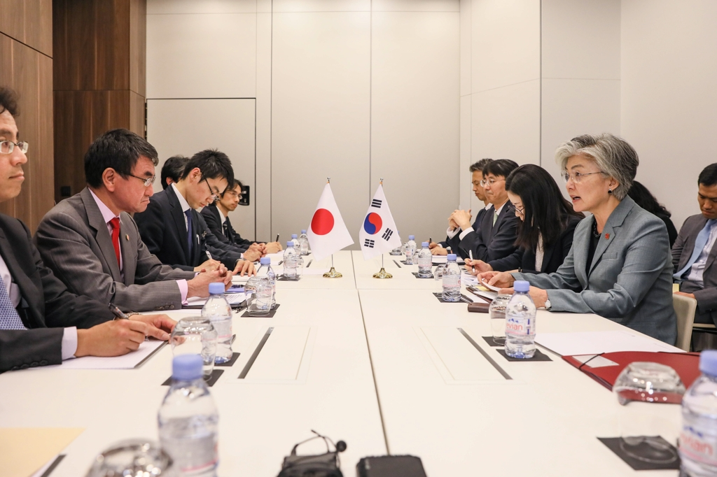 Foreign Minister Kang Kyung-wha (R) speaks during talks with her Japanese counterpart, Taro Kono, on the margins of the Ministerial Council Meeting of the Organization for Economic Cooperation and Development in Paris on May 23, 2019, in this photo provided by South Korea's foreign ministry. (Yonhap)