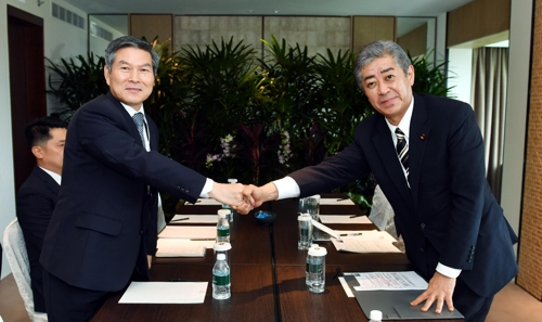 South Korean Defense Minister Jeong Kyeong-doo (L) shakes hands with Japanese Defense Minister Takeshi Iwaya in Singapore on June 1, 2019. (Yonhap)