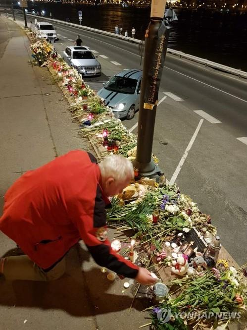 A Hungarian citizen lays a flower at a makeshift altar near the Margit bridge over the Danube River in Budapest on June 7, 2019, to pay tribute to the victims of a deadly boat sinking. (Yonhap)