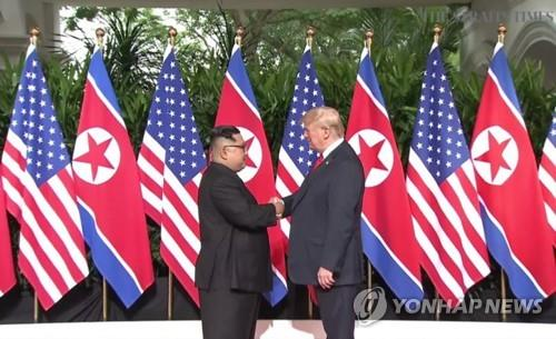 U.S. President Donald Trump (R) shakes hands with North Korean leader Kim Jong-un ahead of their historic summit at the Capella Hotel in Singapore on June 12, 2018. (Yonhap)