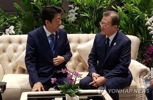 This photo, provided by the presidential office Cheong Wa Dae, shows South Korean President Moon Jae-in (R) having a conversation with Japanese Prime Minister Shinzo Abe prior to a summit of the Association of Southeast Asian Nations and three Northeastern Asian countries -- South Korea, China and Japan -- in Bangkok on Nov. 4, 2019. (PHOTO NOT FOR SALE) (Yonhap)