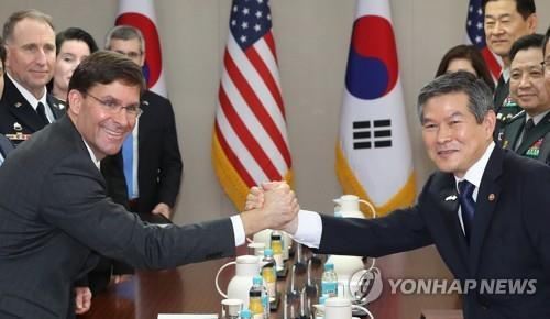 South Korean Defense Minister Jeong Kyeong-doo (R) and U.S. Secretary of Defense Mark Esper clasp hands during their talks at the defense ministry in Seoul on Aug. 9, 2019. (Yonhap)