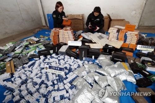 Coast Guard officers display smuggled goods, seized in 2019, at a warehouse in the city of Incheon, west of Seoul, on Jan. 6, 2020. (Yonhap)