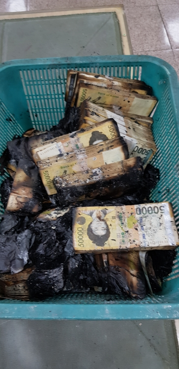 This photo provided by the Bank of Korea (BOK) shows stashes of 50,000-won banknotes damaged by fire. The BOK said on Jan. 15, 2020, that about 640 million banknotes and coins, totaling 4.35 trillion won (US$3.75 billion), had to be replaced in 2019 due to damage or contamination. (PHOTO NOT FOR SALE) (Yonhap)