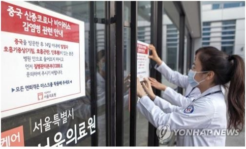 Hospital employees at Seoul Medical Center in the South Korean capital put up a notice informing people of risks associated with the Wuhan coronavirus on Jan. 24, 2020. (Yonhap)