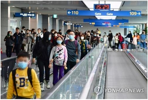 This file photo taken Jan. 23, 2020, shows people at Incheon International Airport west of Seoul wearing masks as they move through the passenger terminal amid Wuhan coronavirus fears. (Yonhap)