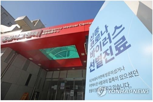 This file photo shows a sign by the entrance of the National Medical Center in Seoul asking people with novel coronavirus symptoms to go to a separate screening clinic within its premises. (Yonhap)