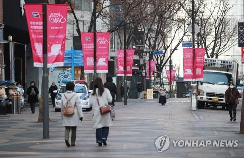 A few people walk on a street in Myeongdong in downtown Seoul on Feb. 8, 2020. The normally busy tourist district was nearly empty amid growing fears of the new coronavirus. (Yonhap)