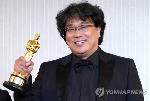 "South Korean director Bong Joon-ho holds up an Oscar trophy at a press conference held at the London West Hollywood in Los Angeles on Feb. 9, 2020 (local time), after his black comedy film ""Parasite"" took four titles at the 92nd annual Academy Awards. (Yonhap)"