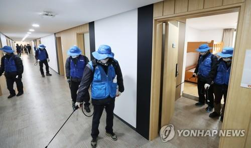 Workers at a youth hostel in Suwon, 46 kilometers south of Seoul, disinfect a room on Feb. 17, 2020, that will be used as a temporary self-quarantine facility by people suspected of having contracted the novel coronavirus. (Yonhap)