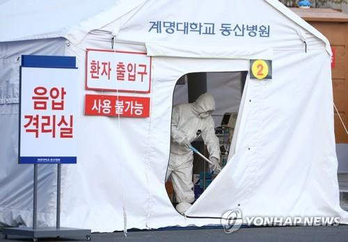 Workers erect a temporary negative-pressure quarantine room outside a hospital in Daegu, 300 kilometers southeast of Seoul, on Feb. 21, 2020, to accommodate suspected coronavirus patients waiting for their test results. (Yonhap)