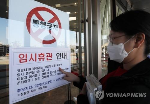 A visitor reads a notice of closure on a gate of the National Library of Korea, Sejong, on Feb. 23, 2020. (Yonhap)