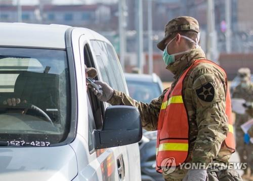 A military guard at U.S. Army Garrison Humphreys in Pyeongtaek, Gyeonggi Province, checks the temperature of a driver to screen entrants to the compound for the novel coronavirus on Feb. 28, 2020, in the photo provided by United States Forces Korea. (PHOTO NOT FOR SALE) (Yonhap)