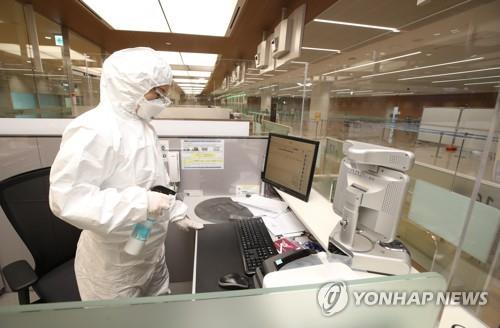An immigration official clad in protective gear disinfects his desk at an immigration stand exclusively for inbound visitors with symptoms of the new coronavirus at Incheon airport, west of Seoul, on April 8, 2020. (Yonhap)