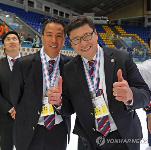 In this photo provided by the Korea Ice Hockey Association on April 28, 2017, South Korean men's hockey head coach Jim Paek (R) and his assistant Richard Park pose for pictures after South Korea finished in second place at the International Ice Hockey Federation (IIHF) World Championship Division I Group A in Kiev, Ukraine. (PHOTO NOT FOR SALE) (Yonhap)