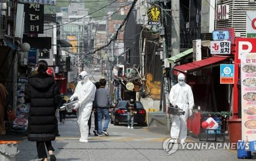 Quarantine officials spray disinfectant on a street in the international district of Itaewon in Seoul, on May 11, 2020, as scores of new cases were reported from people who recently visited entertainment places in the area. (Yonhap)