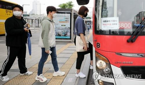 People wearing masks board a bus in Seoul on May 26, 2020. Health authorities said all bus, taxi and airplane passengers are required to wear masks to prevent COVID-19 infection. (Yonhap)